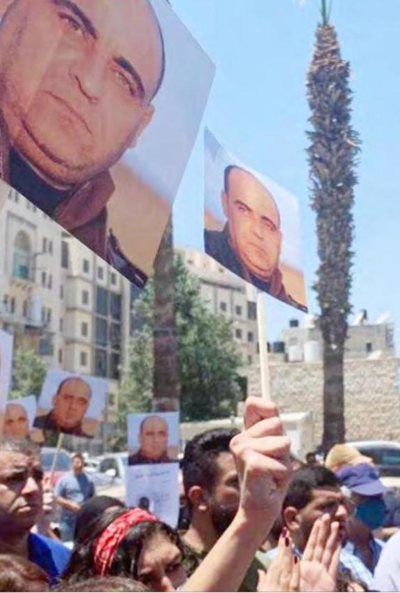 """Ramallah'ta göstericiler öldürülen Banat fotoğraflarıyla """"Abbas Defol!""""diyorlar."""